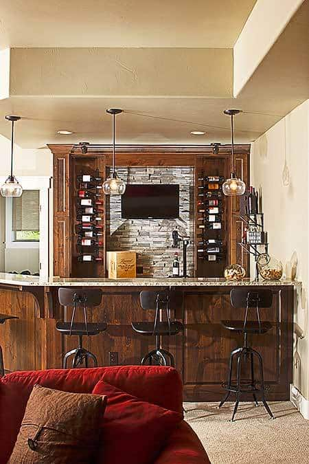 A closer look at the wet bar shows a pair of single column wine racks and a granite countertop lined with brown barstools.