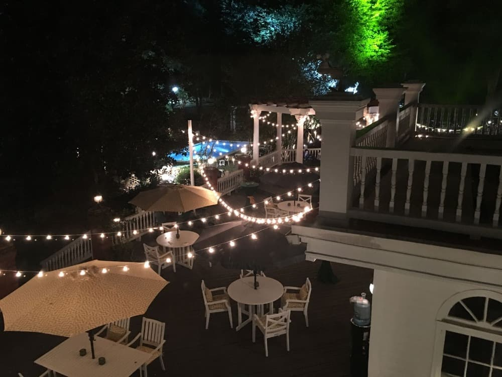A night time view of the backyard featuring multiple outdoor dining table sets with lovely lighting. Images courtesy of Toptenrealestatedeals.com.