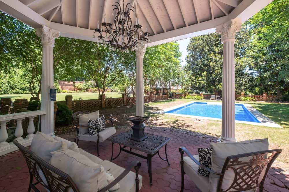 Here's the covered patio area featuring a set of nice seats with a matching center table. The home also has a rectangular swimming pool. Images courtesy of Toptenrealestatedeals.com.