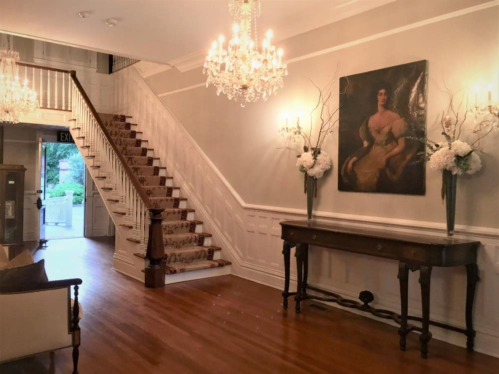 The entry hall boasts gorgeous chandelier and a side table, along with an elegant wall art decor lighted by wall lights. Images courtesy of Toptenrealestatedeals.com.
