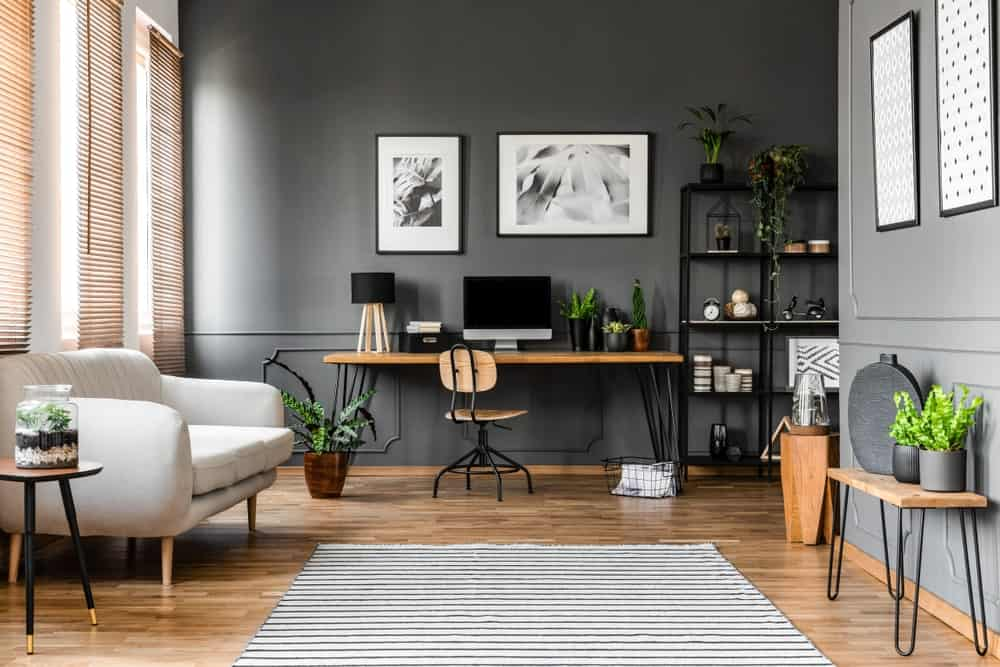 Gray Home Office in an open concept house showcasing wooden desk and chair, black shelving, potted plants, hardwood flooring and black and white artworks against gray wainscoted walls.