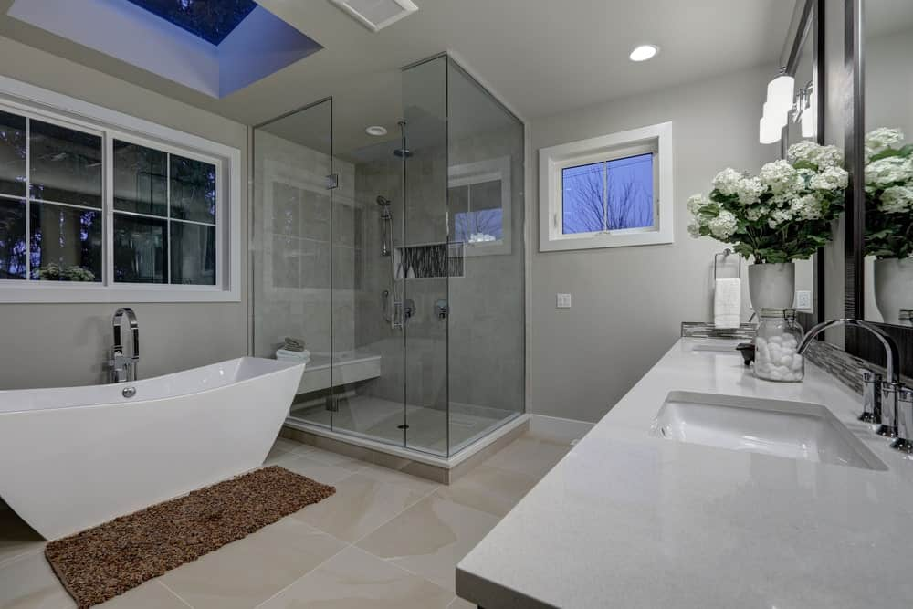 Gray primary bathroom with walk-in shower, dual sink vanity, white framed windows, brown rug over beige tiled flooring and a freestanding tub underneath a skylight.