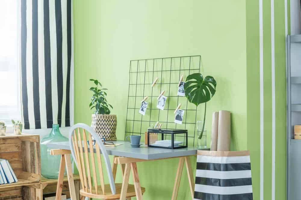 Green Home Office with wooden desk and chair, metal accessories, wooden shelving, small potted plants and a white framed window covered in black striped curtains.