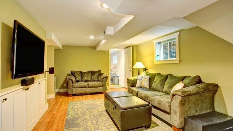 A cozy and homey basement with green walls and white arched ceiling that matches with the white wainscoting of the wall where the TV is mounted.