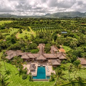 This aerial shot of the large and luxurious estate shows that the earthy tone of the exteriors make it stand out against the surrounding immense land filled with vegetation and farmland. This view shows that the large pool is placed facing the bluff cliff that looks out to the ocean. Images courtesy of Toptenrealestatedeals.com.
