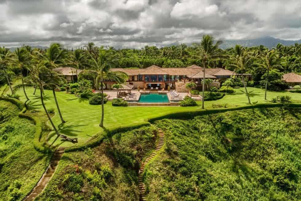 The gorgeous estate is facing a wide bluff cliff overlooking the ocean. There is also a wide lawn of green grass before the edge bordered by hedges and tall tropical trees to set a beautiful scenery for those looking out the large glass windows or those at the pool area. Images courtesy of Toptenrealestatedeals.com.