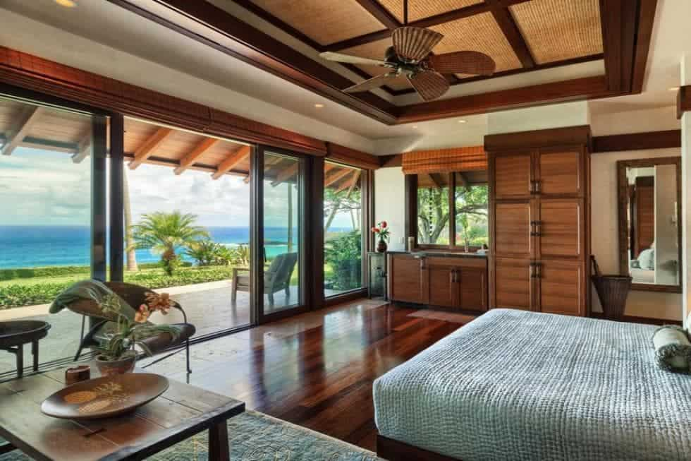 The tray ceiling of this bedroom has exposed wooden beams matching the dark hardwood flooring brightened by the abundance of natural lighting coming in from the surrounding glass windows and wide sliding glass doors that offer a beautiful view of the landscaping beyond. Images courtesy of Toptenrealestatedeals.com.