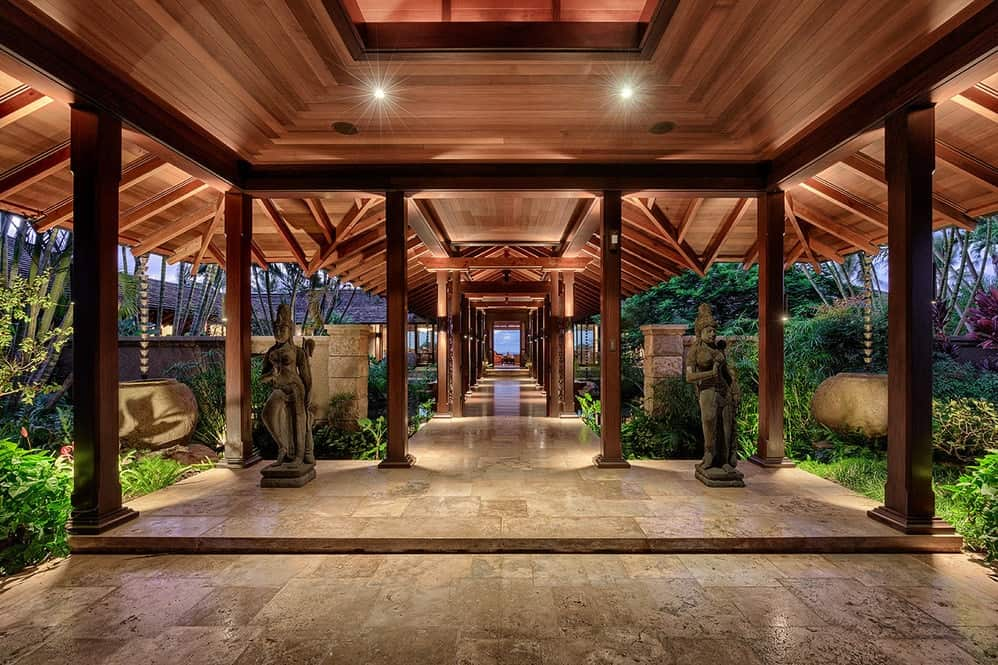 The main entrance and foyer has tall wooden columns that hold up the lovely wooden ceiling with exposed wooden beams. The entry is also flanked by a couple of stone statues to set the vibe. Images courtesy of Toptenrealestatedeals.com.