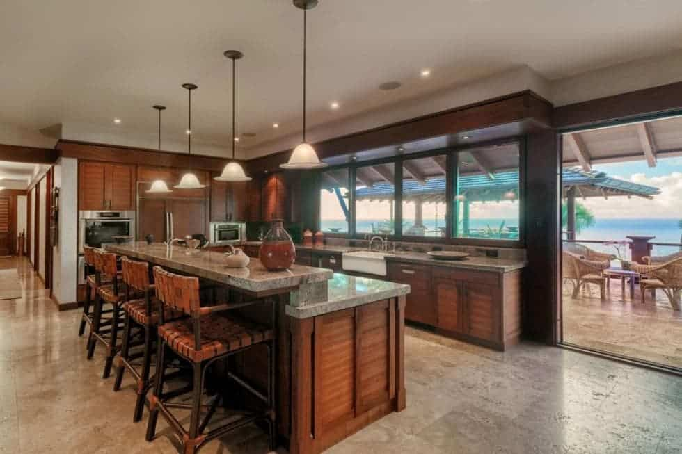 The large kitchen has dark brown cabinetry that stands out against the beige marble flooring that matches the ceiling. From the ceiling hangs four pendant lights over the kitchen island fitted with a second tier countertop for the breakfast bar paired with woven wicker stools. Images courtesy of Toptenrealestatedeals.com.