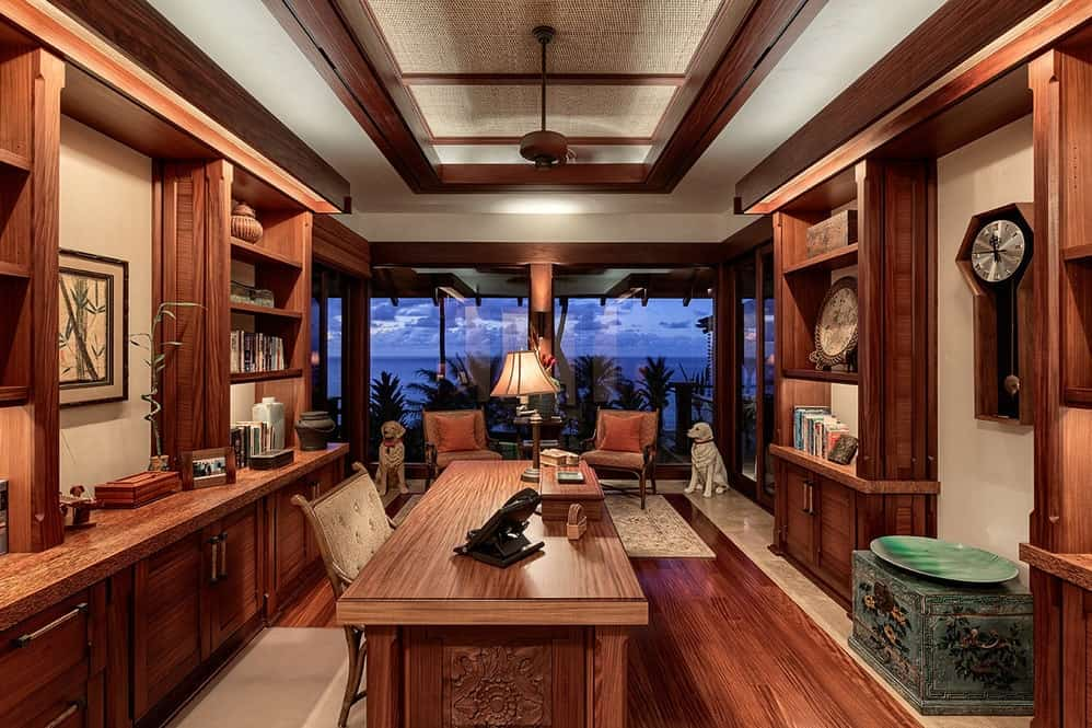 The home office of the estate has a charming and elegant dark hardwood flooring that matches perfectly with the wooden desk and the built-in wooden shelves that line the walls with wooden molding that matches the tray ceiling accents. Images courtesy of Toptenrealestatedeals.com.