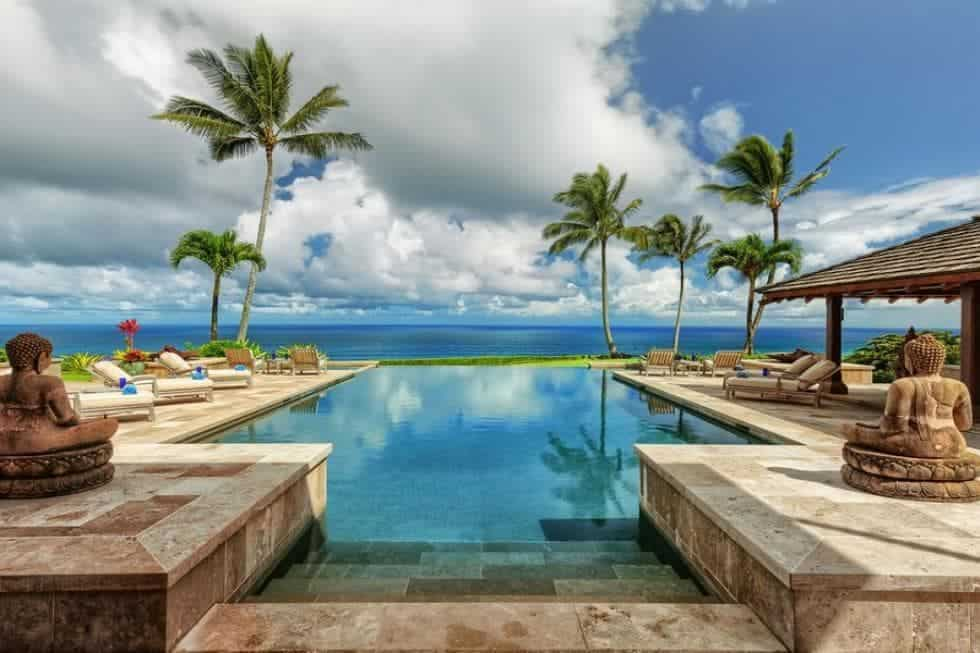 This view of the ocean from the vantage of the pool entrance is adorned with tall tropical trees that serve as a charming background for the sitting areas on the sides of the pool with cushioned lawn chairs. Images courtesy of Toptenrealestatedeals.com.