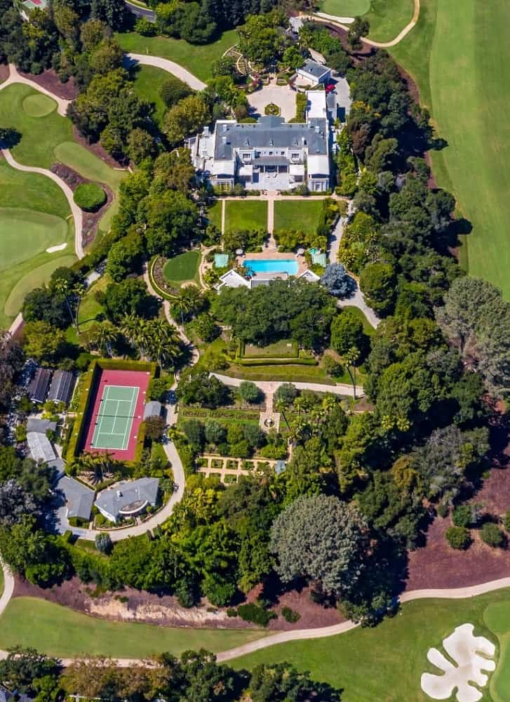 The massive property is on full display in this aerial shot that shows various outdoor areas like a pool and tennis court amidst the thick collection of tall trees and lush landscaping. Images courtesy of Toptenrealestatedeals.com.