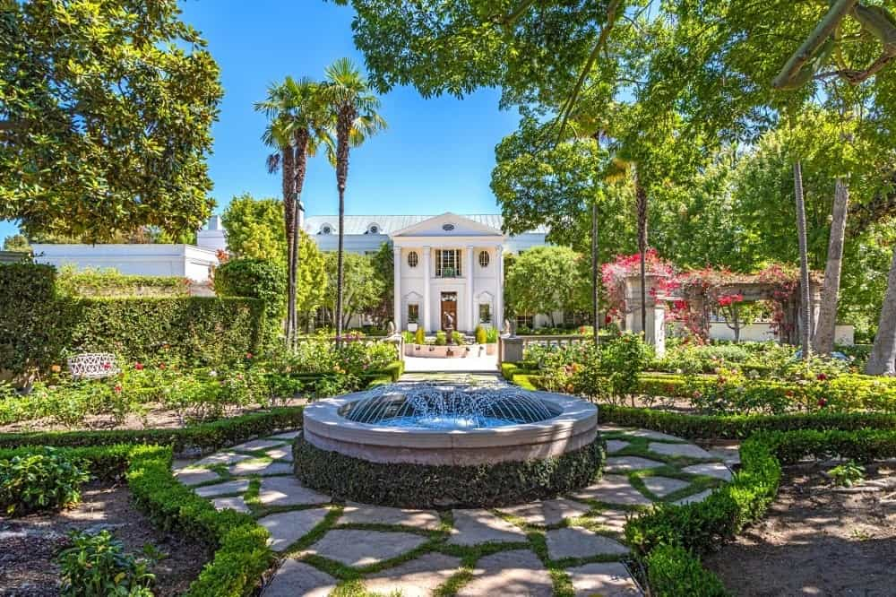 The front yard view of the home boasts of a large garden with a circular fountain and a view of the house in the distance. Images courtesy of Toptenrealestatedeals.com.