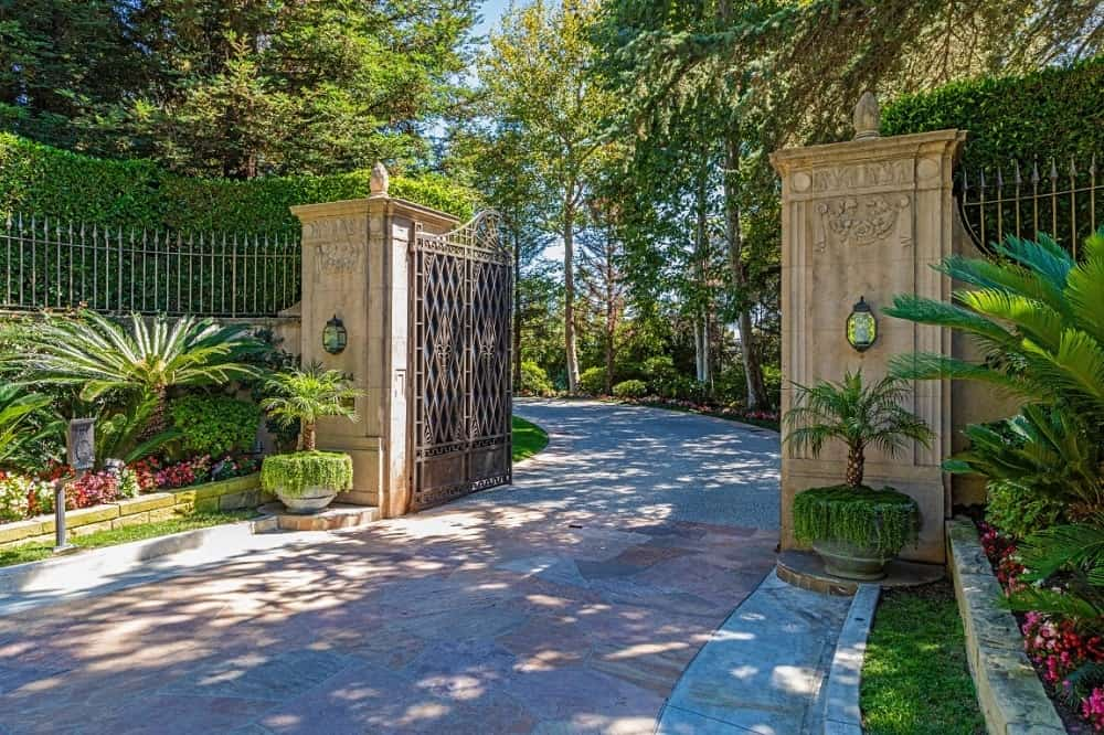 The grand entry gate has large wrought iron gates with two thick pillars of stone complemented by charming potted plants and wall sconce. Images courtesy of Toptenrealestatedeals.com.