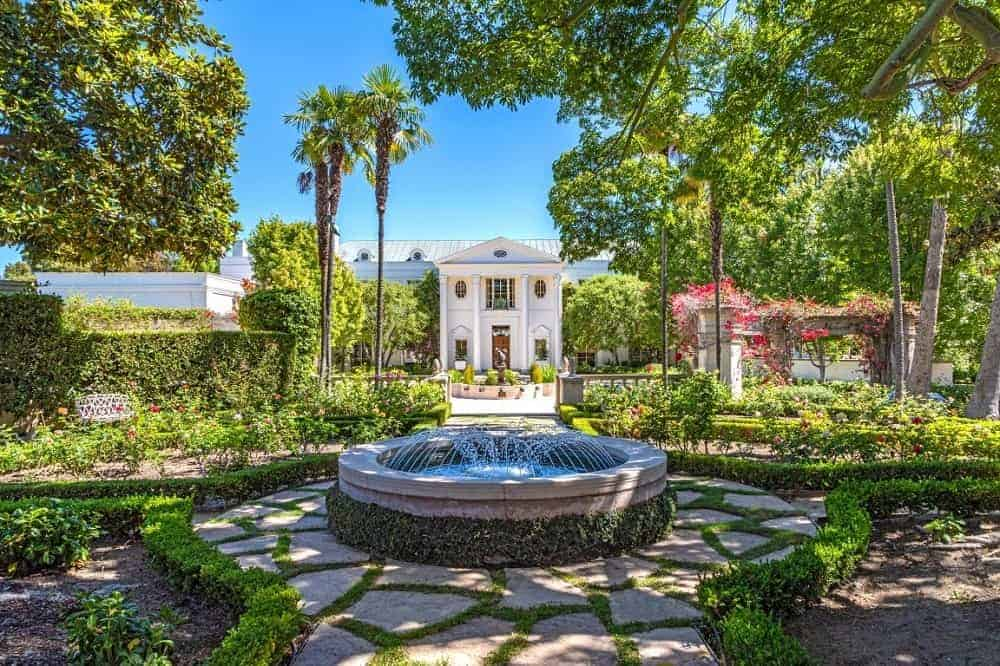 A look at the house's exterior along with its gorgeous garden and landscaping. There's a fountain in the yard as well, with <a class=