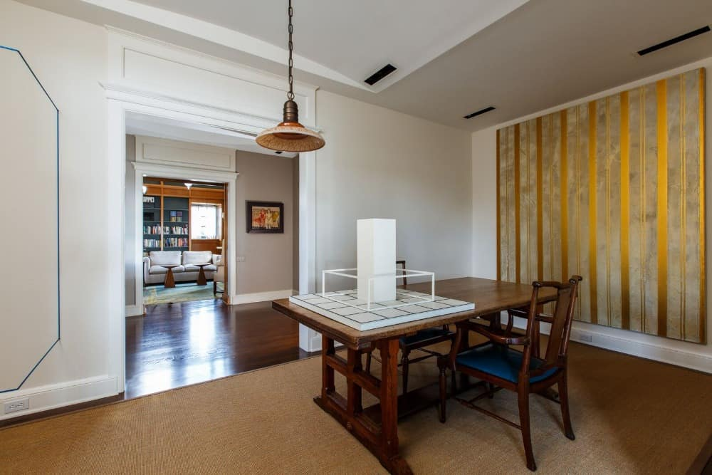 This table set near the library room offers a multiuse table. The room has an area rug covering the hardwood flooring. Images courtesy of Toptenrealestatedeals.com.