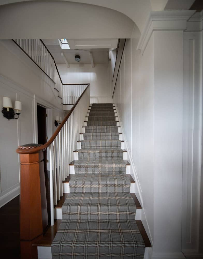 The house's staircase features carpeted steps, white painted railings and a wooden handrail. Images courtesy of Toptenrealestatedeals.com.