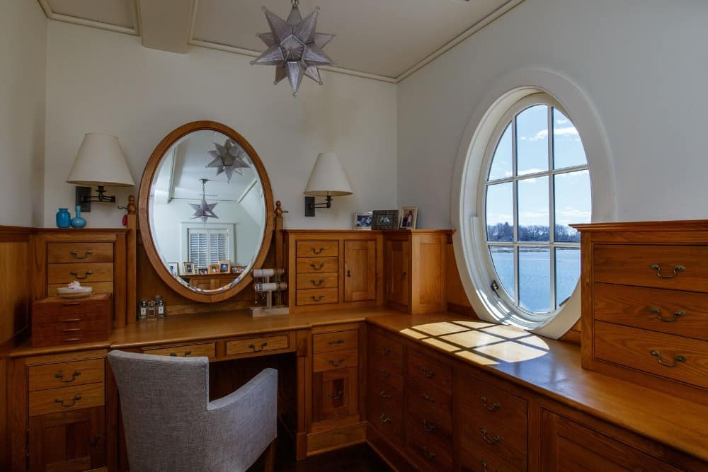 A large powder room featuring a built-in desk with multiple drawers and is lighted by wall lights. Images courtesy of Toptenrealestatedeals.com.