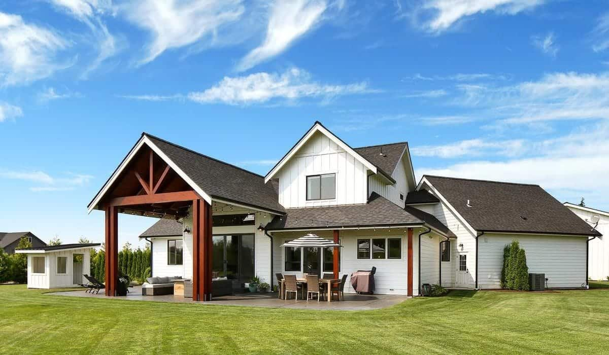 The outdoor view from the backyard shows the white siding of the house accented with decorative beams.
