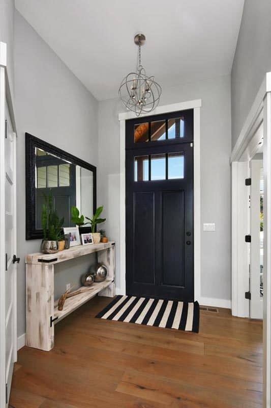 The home's foyer has a dark wood front door complemented by a striped rug. It includes a spherical chandelier and a rustic console table paired with a large framed mirror.