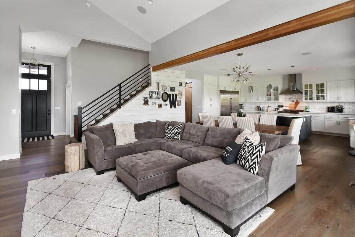 Across the foyer is the living room that opens to the dining and kitchen. It has velvet gray sectional and a matching ottoman sitting over the beige patterned rug.