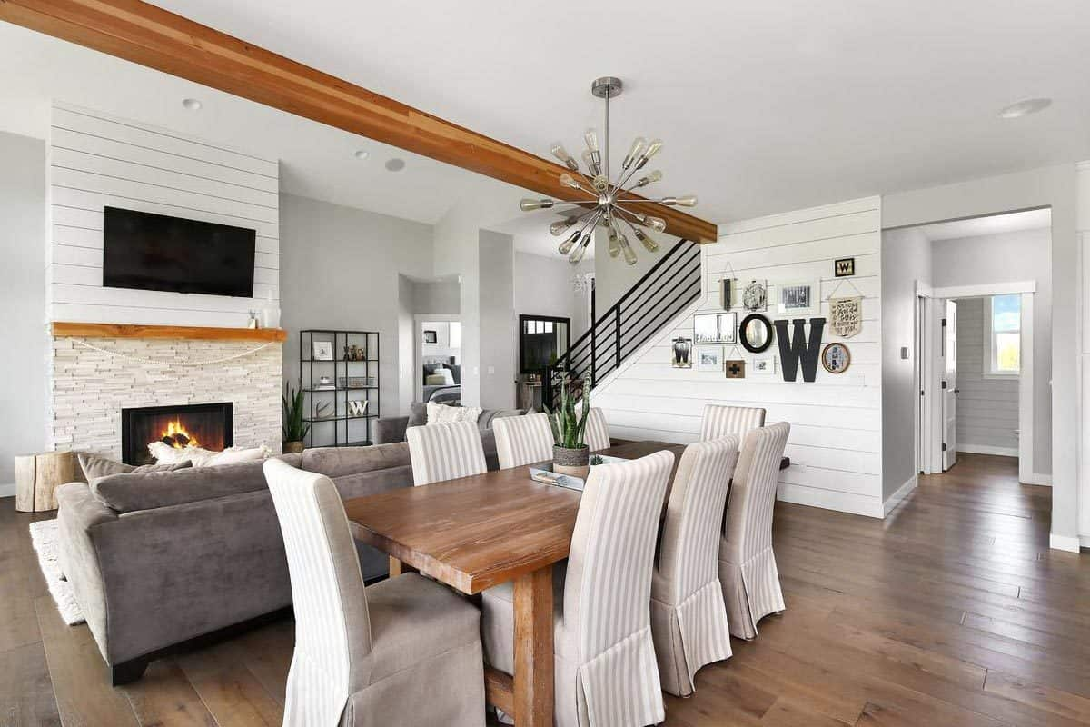 The dining area with a wooden rectangular table and striped high back chairs is situated behind the gray sofa.