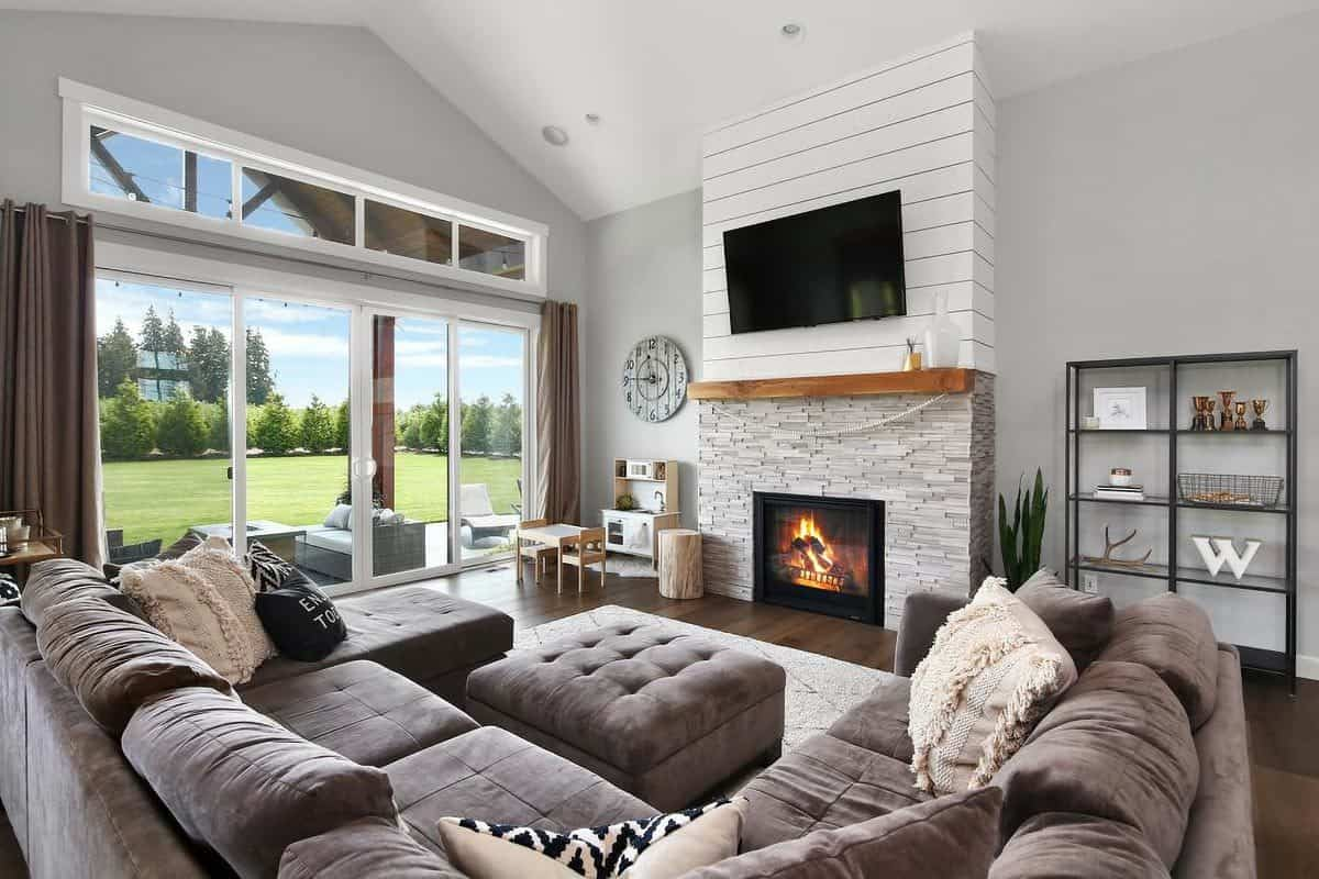 The velvet sectional faces the brick fireplace and the wall-mounted TV flanked by a metal shelving unit and a play area.