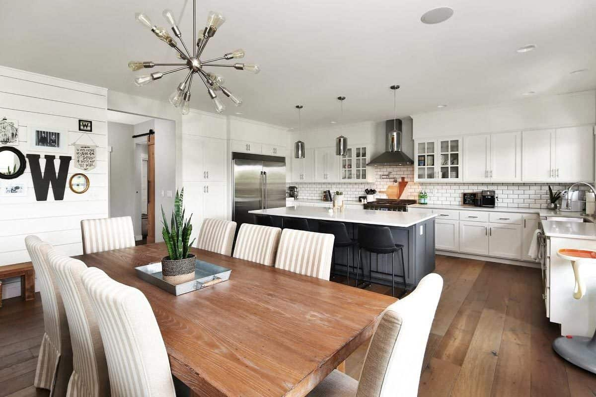 The wide plank flooring and dining table soften the sleek white walls and cabinetry in the kitchen.
