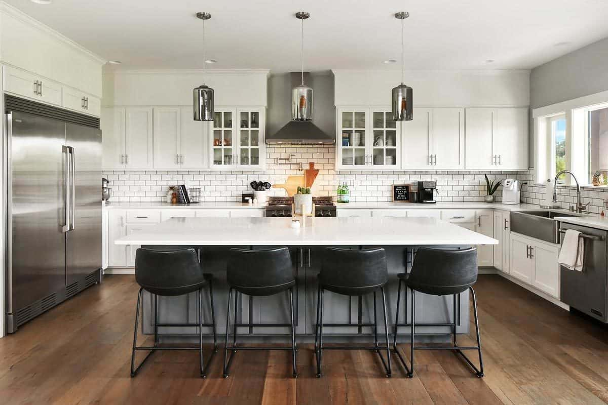 The kitchen showcases a large breakfast island lined with black leather stools and chrome pendant lights.