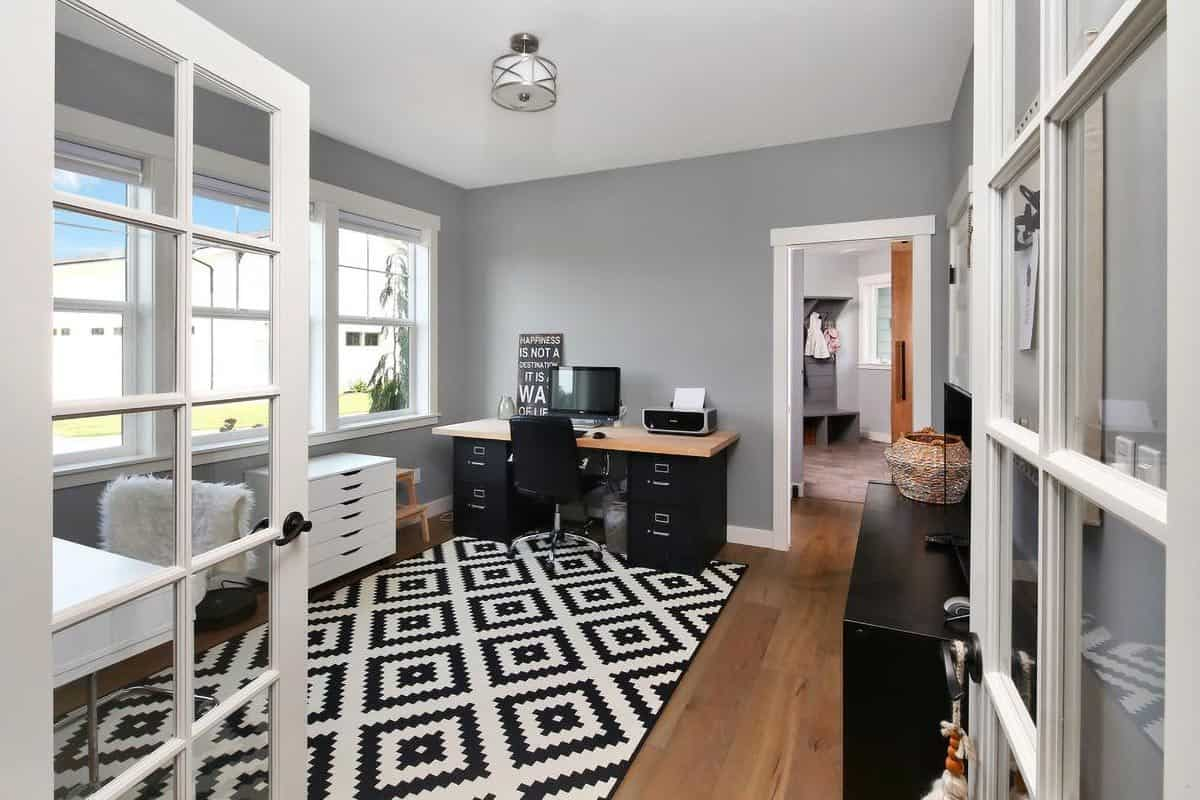 A french door opens to the home office with an eye-catching patterned rug and a wooden desk complemented by a swivel chair.