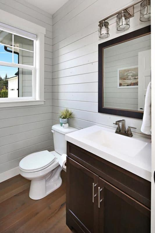 The powder room has a dark wood vanity and a toilet underneath the white framed window.