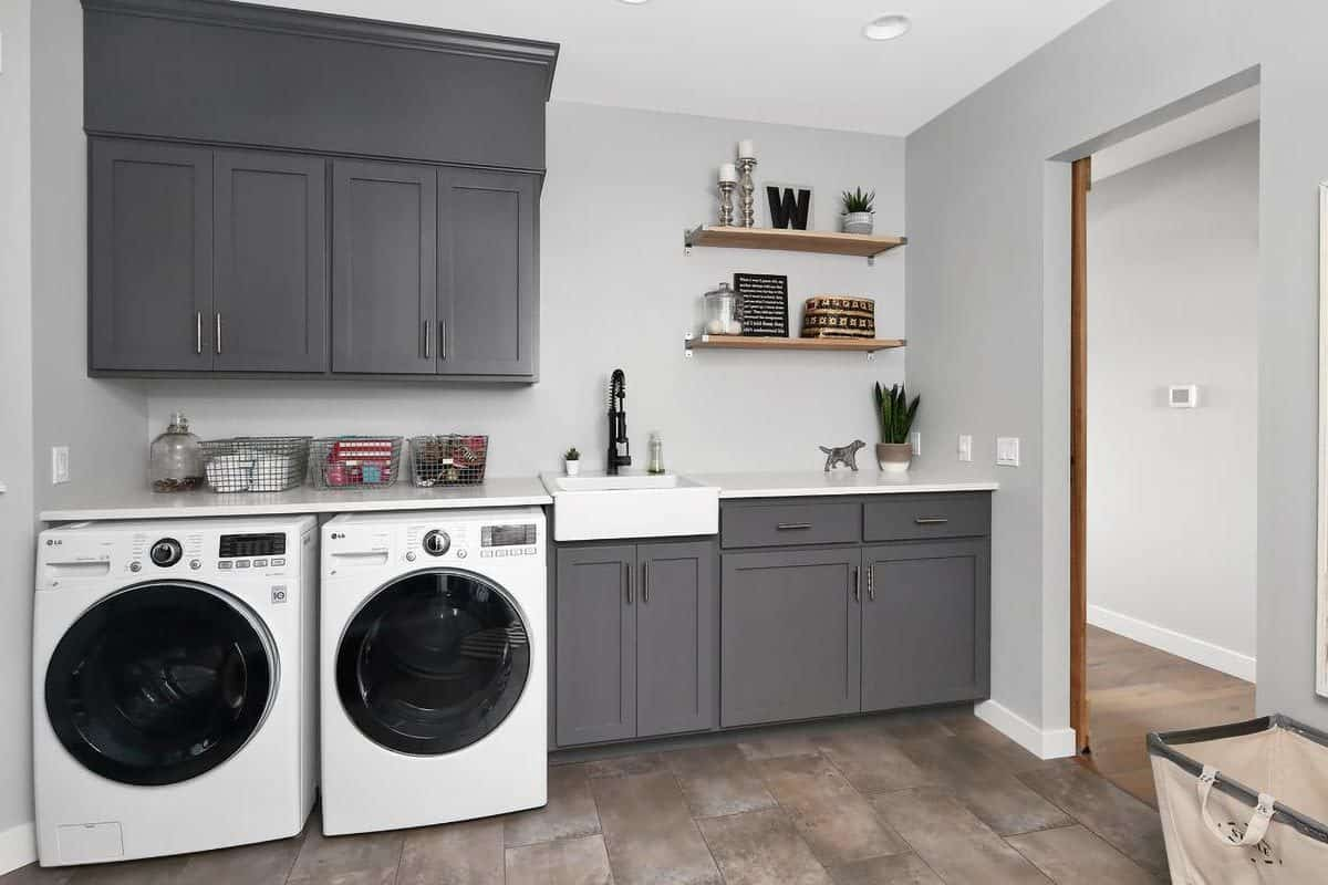 The utility room is equipped with front load washer and dryer along with a farmhouse sink paired with a pull-down sprayer.