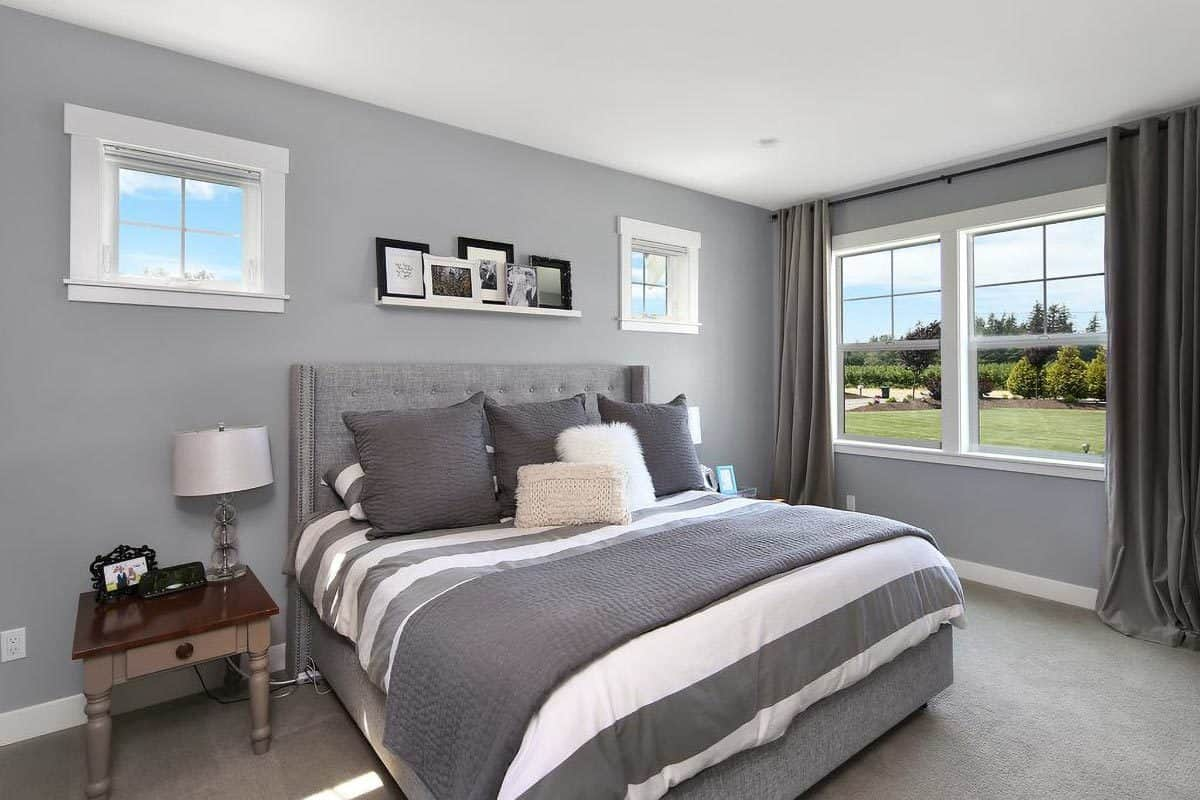 The primary bedroom boasts a gray tufted bed and white framed windows overlooking the expansive garden.