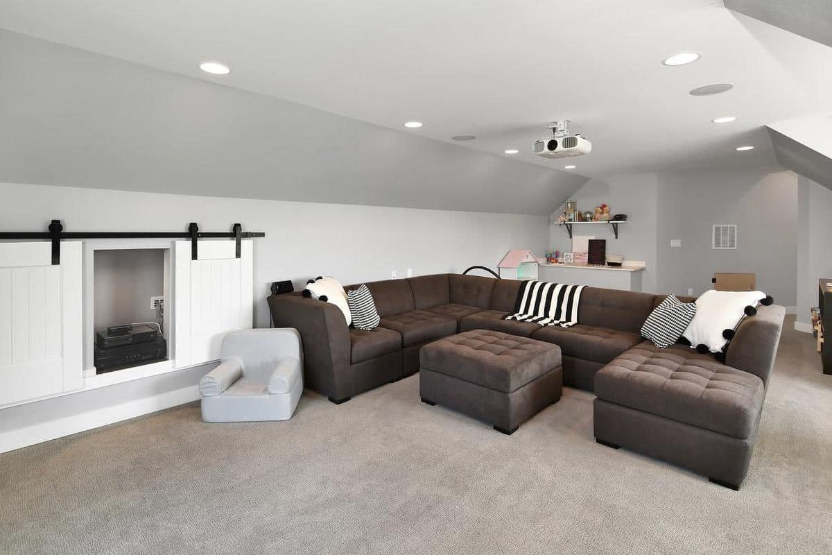 The media room is filled with a tufted sectional and a small playing area behind it.