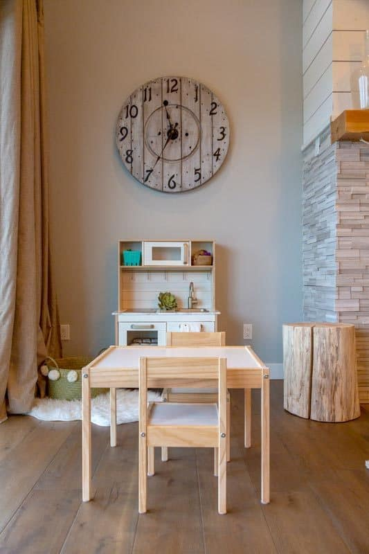 Here's a closer look at the play area. It has a wooden kitchen set under a wall clock and a table paired with matching chairs.