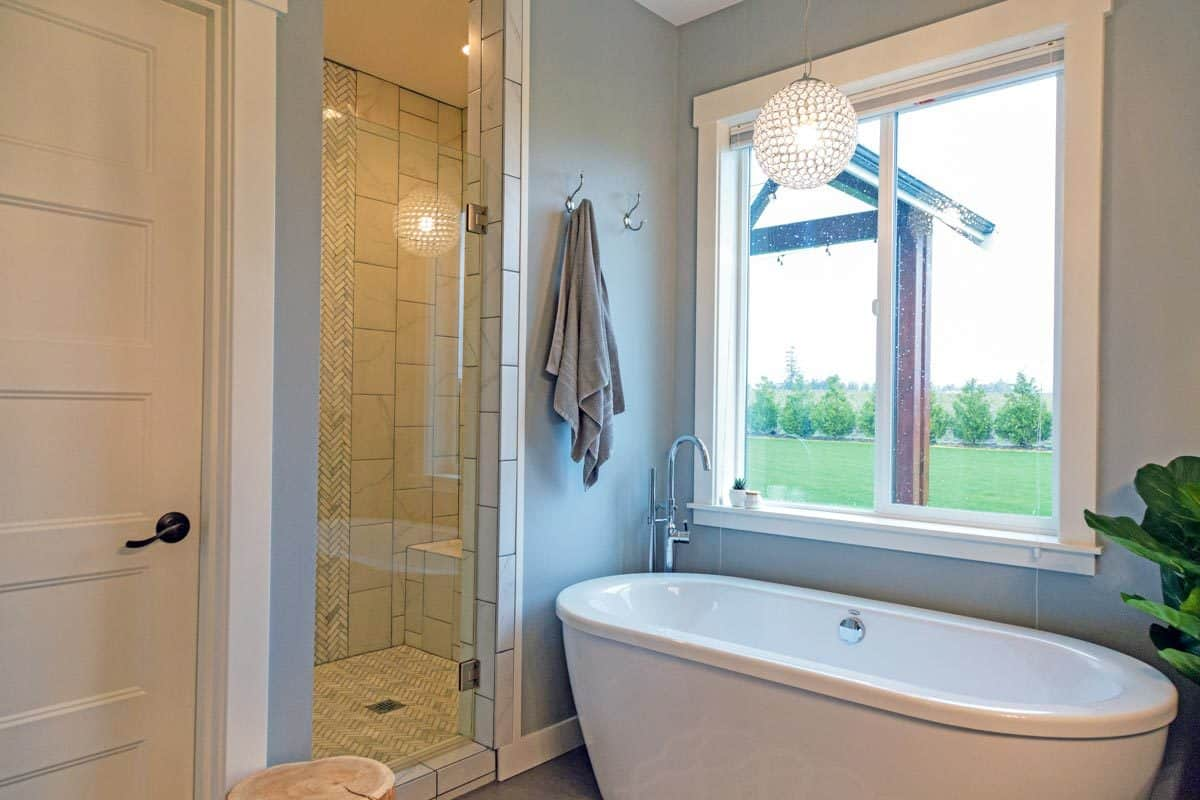 The primary bathroom illuminated by recessed lights from the shower area and a spherical pendant hanging above the bathtub.