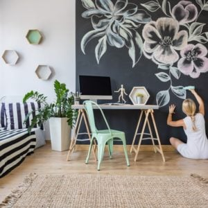 A woman doing a large floral chalk wall art mural in her bright room.