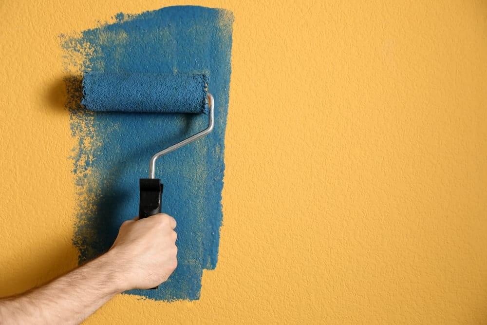 A man painting blue paint over the yellow wall.