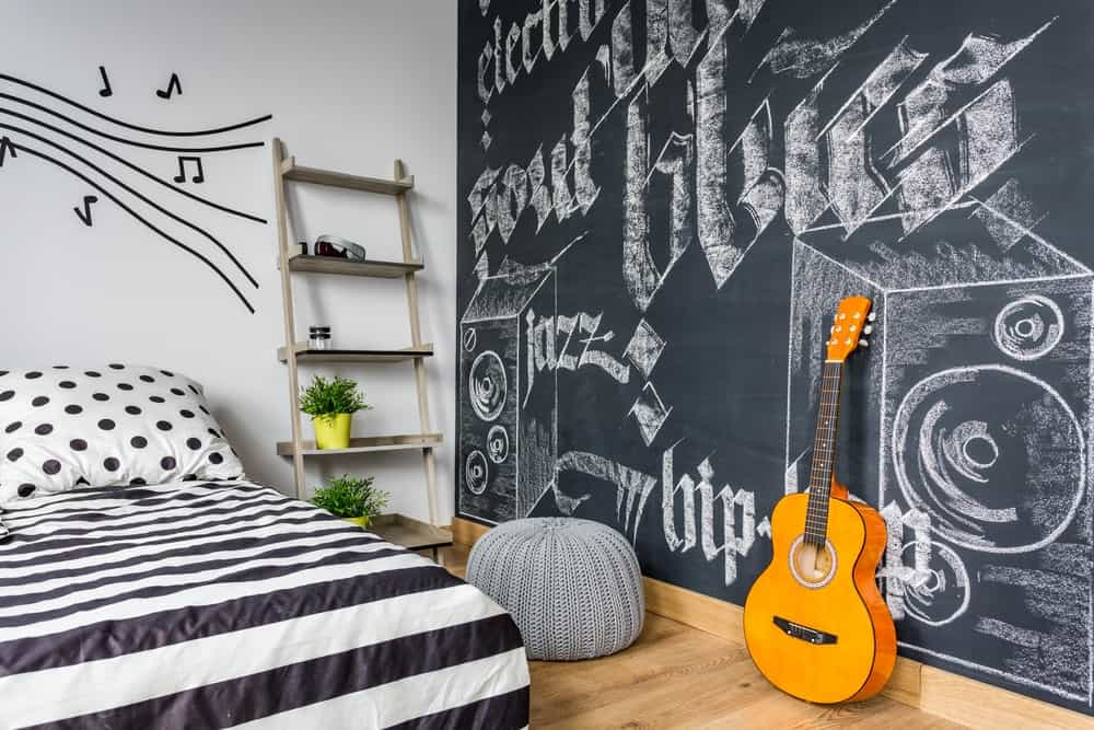 A bedroom with a chalkboard wall filled with word art.