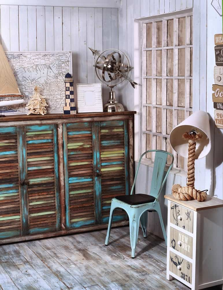 A corner of a house with distressed walls and flooring decorated with an antique shabby chic cabinet.