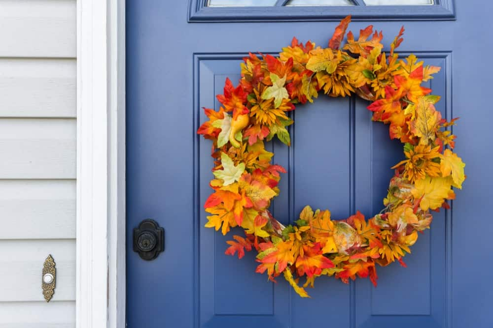 The blue wooden front door of the house complemented by a wreath of autumn leaves.