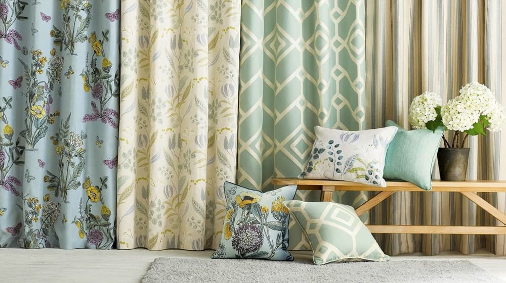 A display of various pillows and curtains in varying shades of green and patterns.