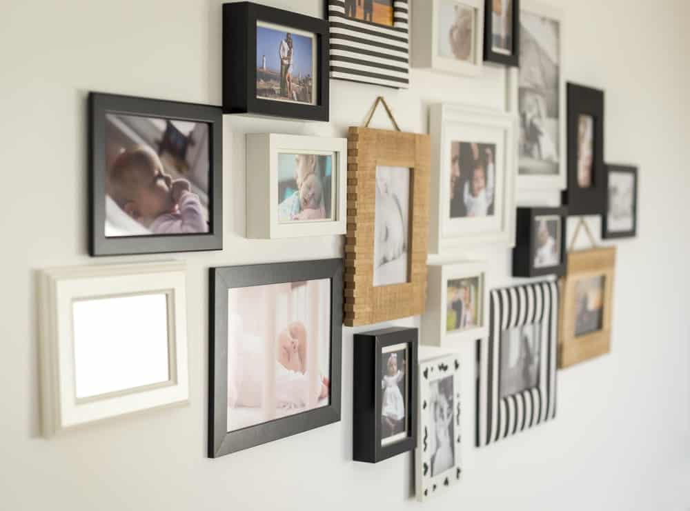 Various personal photos in different frames mounted on the wall for a decorative effect.