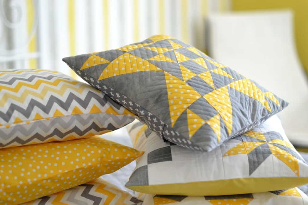 A bunch of throw pillows in different patterns of yellow covers.