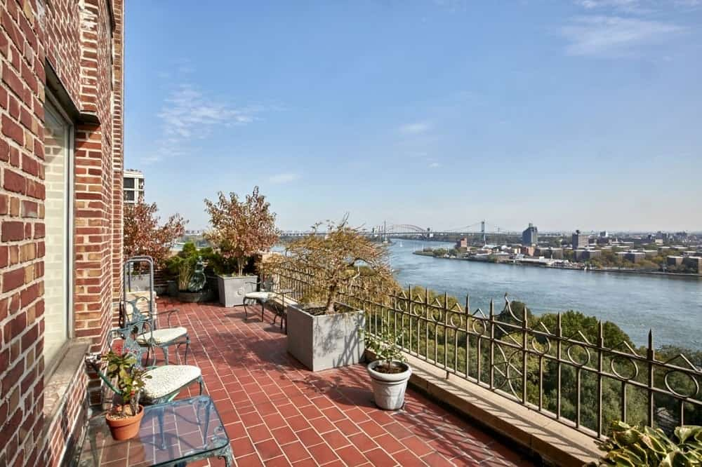 The patio and balcony of the penthouse with charming brick flooring and amazing view of the river. Images courtesy of Toptenrealestatedeals.com.