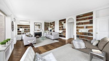 The living room has a bright white ceiling and surrounded by built-in book shelves warmed by a charming fireplace. Images courtesy of Toptenrealestatedeals.com.