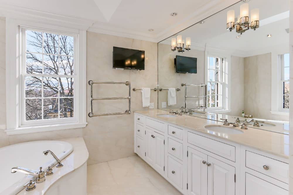 The primary bathroom offers a drop-in soaking tub along with a sink counter with two sinks. Images courtesy of Toptenrealestatedeals.com.