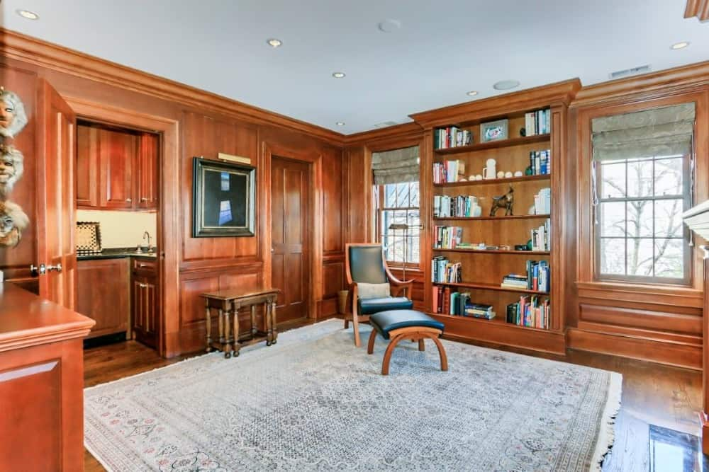 Another look at this living space featuring brown walls and hardwood flooring topped by a large area rug. Images courtesy of Toptenrealestatedeals.com.