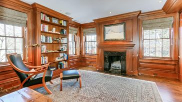 Formal living room featuring brown walls and hardwood flooring. It offers a fireplace and a built-in bookshelf.