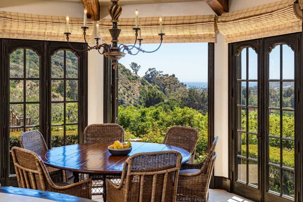 This dining nook offers a wooden round dining table with rattan chairs, set near the doorway and windows overlooking the beautiful surroundings. Images courtesy of Toptenrealestatedeals.com.